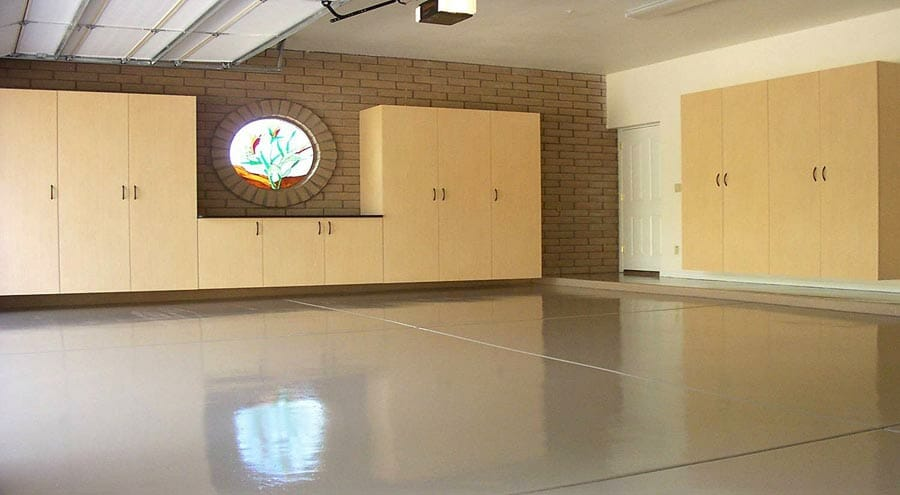 Complete epoxy garage floor in large garage with custom cabinetry