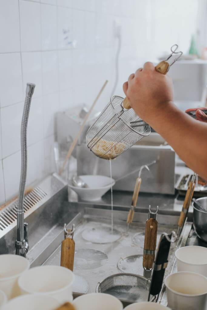 Dish washer in commercial kitchen