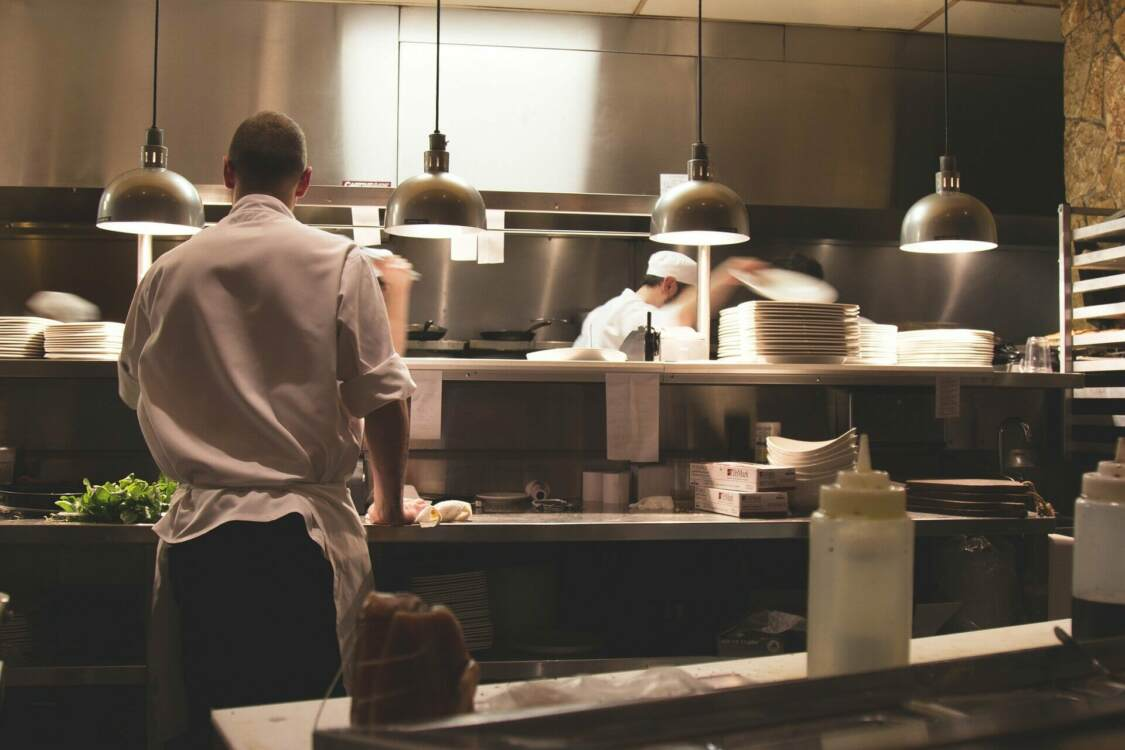 Waiters and cooks in busy commercial kitchen