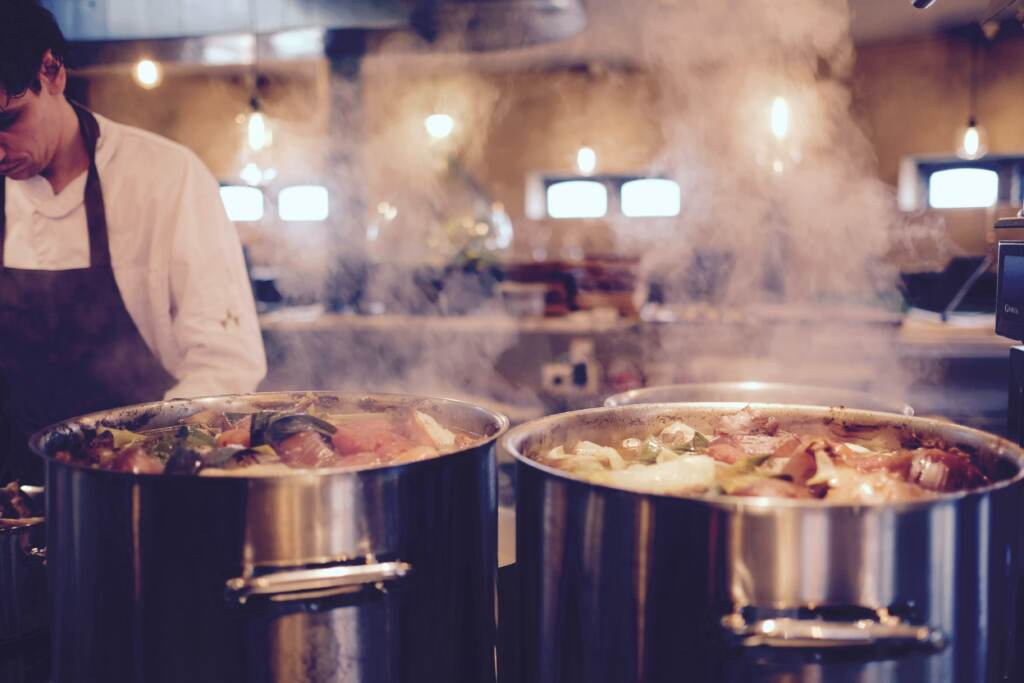 Man working next to full pots on stove in commercial kitchen