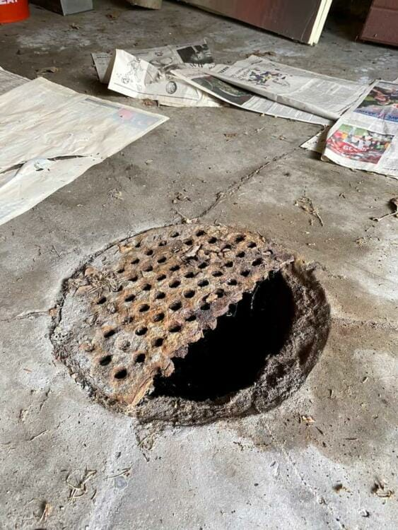 A rusty garage floor drain cover that has partially caved in | Metal drain grate