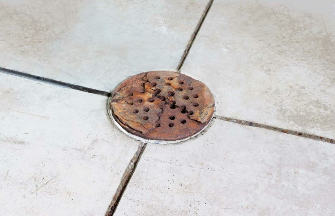 A rusted and cracked Home Depot drain cover